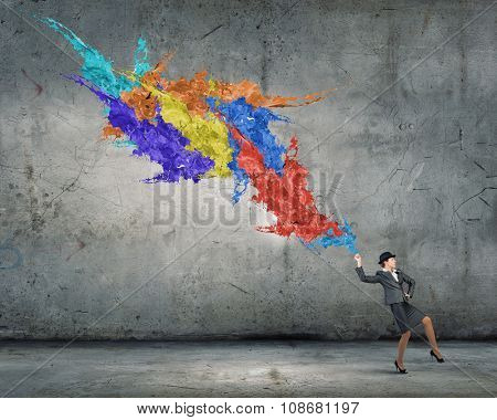 Creative businesswoman in suit and hat with paints splash