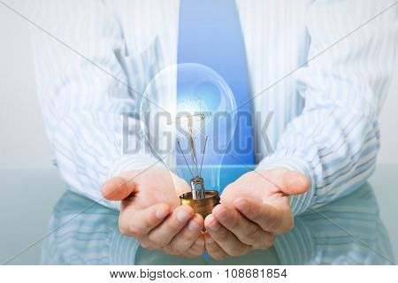 Hands of businessman holding with care glass light bulb