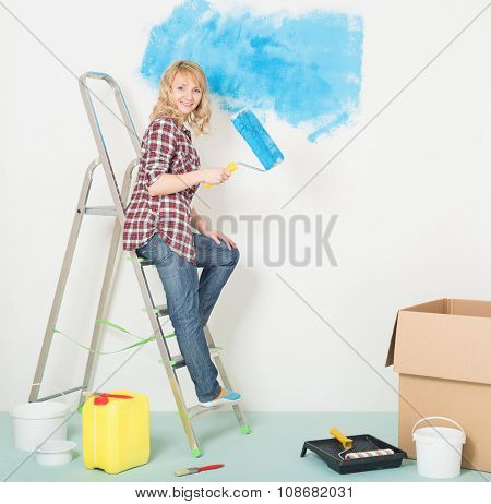 Happy woman makes repairs at home. Smiling beautiful young woman with roller and brush on a ladder. Woman painting wall at room.