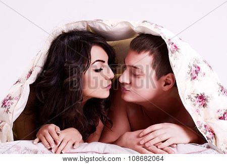 Portrait of happy loving couple under a warm blanket