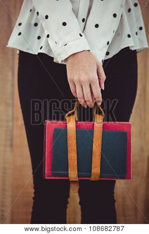 Cropped image of woman holding book belt against wooden background