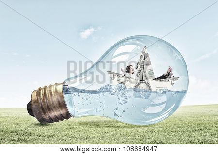 Businesswoman floating on paper boat made of dollar banknote inside light bulb