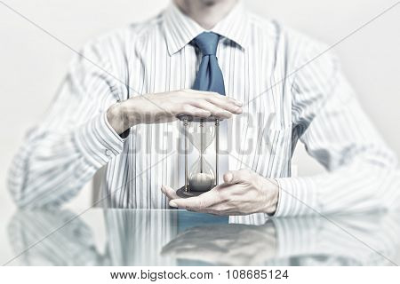 Hands of businessman protecting with palms sandglass