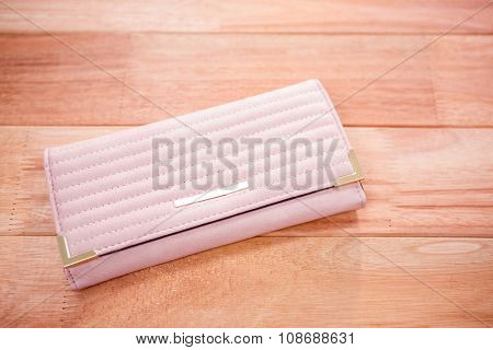 Close up view of a pink wallet on wooden desk