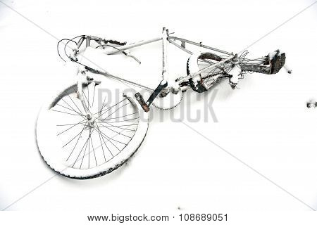 damaged old bycicle in wintertime covered by snow