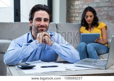 Handsome man paying bills in living room and smiling at the camera