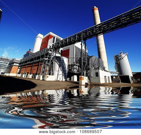 Industrial Factory Against Blue Sky With Reflection