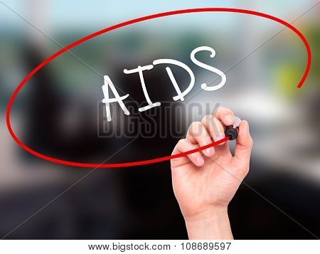 Man Hand writing AIDS with black marker on visual screen.