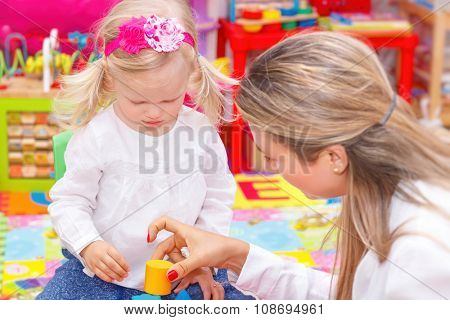Little girl with mother having fun together in the interesting colorful kids room, playing game, communicating and teaching something new