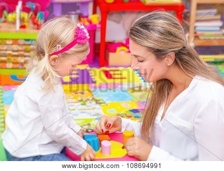 Cute little girl with young beautiful mother playing game in colorful playroom, happy family with pleasure spending time together