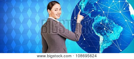 Woman stands near big earth