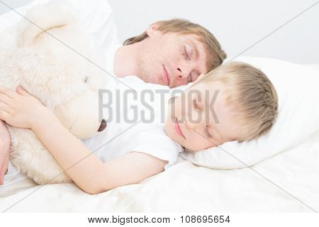 little child and father sleeping in bed