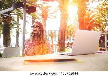beautiful female designer talking on her smart phone while sitting front open laptop computer