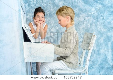 Romantic children playing the white piano. Music and art concept. Vintage, retro style.