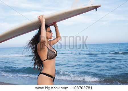 Beautiful surfer girl waiting for the waves to surf on it during summer weekends copy space area