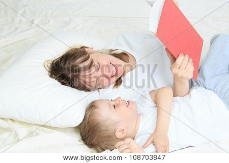 mother and son reading book in bed