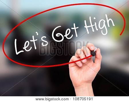 Man Hand writing Let's Get High with black marker on visual screen.