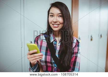 Cheerful student standing next the locker and using smartphone at the university