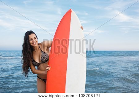 Lovely Latin woman with a perfect figure holding surfboard