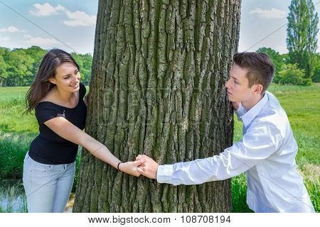 Young Attractive Caucasian Couple In Love Holding Hands Around Tree Trunk