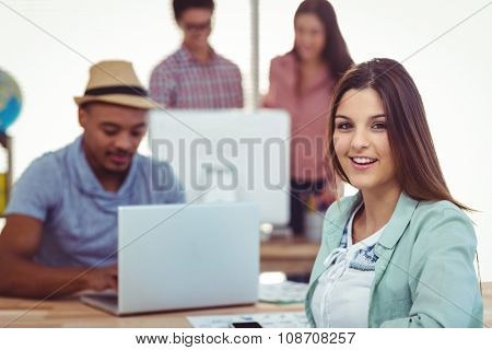 Young creative workers smiling at camera in casual office
