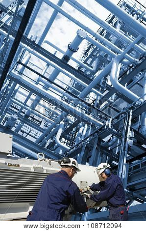 oil workers with large fuel pump inside pipelines constructions