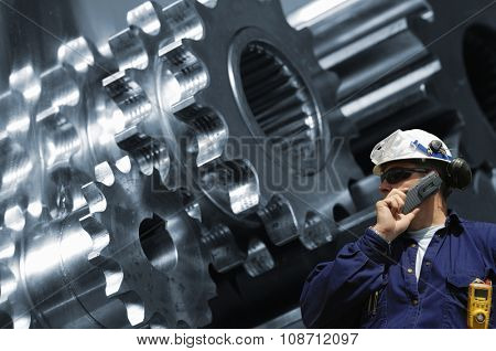 worker, mechanic with machine-parts, cogwheels in background