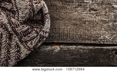 Handmade knitted wool scarf on wooden background