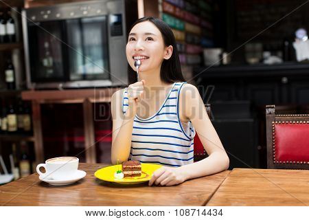 Beautiful Young Woman Sitting And Eating Cake