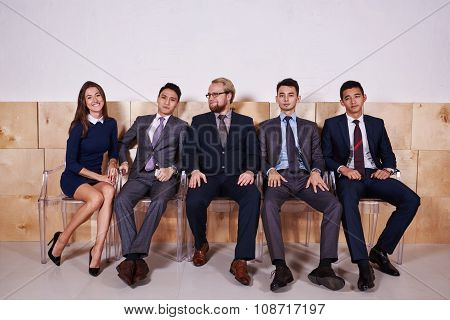 Full length portrait of a multi ethnic people dressed in corporate clothes waiting for start meeting