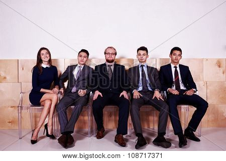 Full length portrait of a multi ethnic people dressed in corporate clothes waiting for meeting