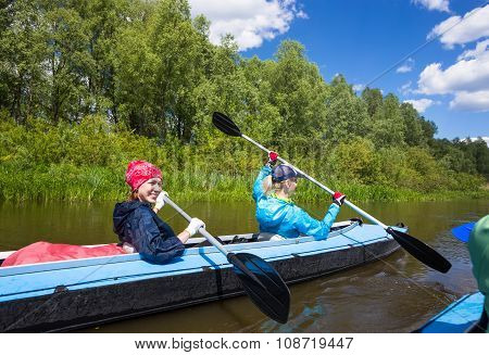 Young people are kayaking on a river in beautiful nature. Summer sunny day outdoor