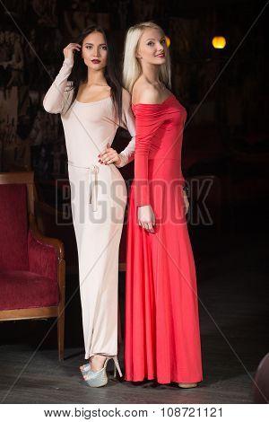 two women Fashion model wearing evening gown, club.