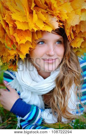 Girl With A Wreath From Yellow Leaves On The Head On The Background Of Autumn Forest