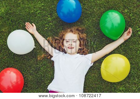 Happy Child Lies On Green Grass With Rainbow Balloons At Summer Park.
