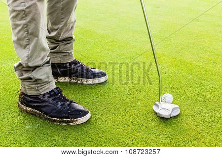Hitting A Golf Ball With A Putter Club