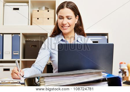 Business woman with laptop in her office taking notes during research