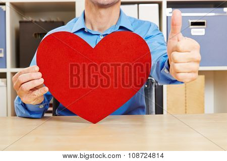 Man with bis red heart holding his thumbs up in the office