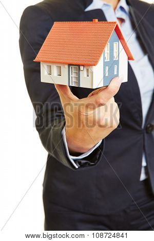 Hands of a female real estate broker holding a small house as concept for a home