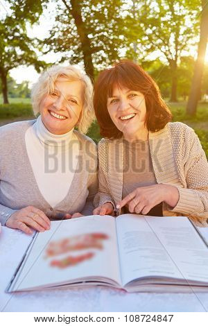 Two smiling elderly women browsing through a cookbook in summer in a garden