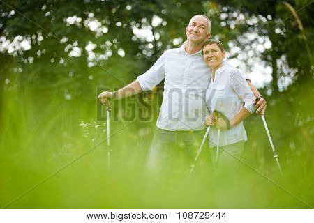 Happy senior couple on summer holiday doing nordic walking