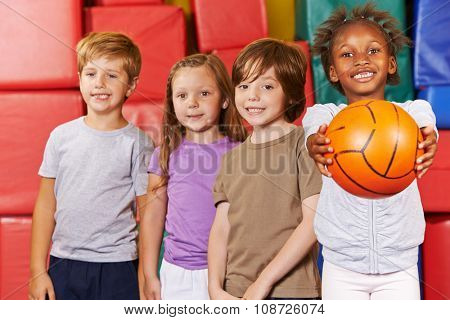 Happy children team with basketball in a gym of a kindergarten