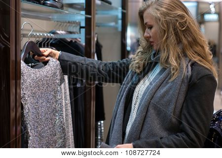 woman  standing in a clothing store and looking at holding a new dress