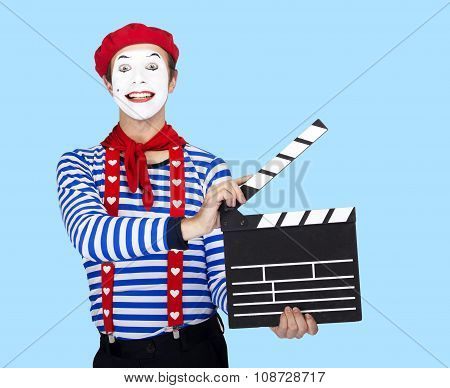 Funny mime actor wearing sailor suit, red beret posing on blue background.
