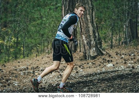 young man runs through forest and smiling