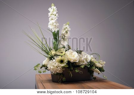 Artificial flowers bouquet in vase on the table