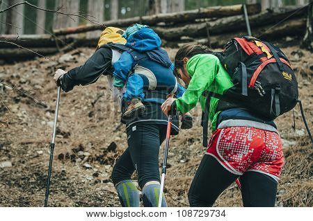 dad and mom and their child walking on a forest trail in mount