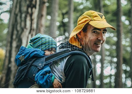 closeup of father carries his child on his back in a backpack