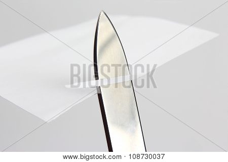 Blade Of A Sharp Knife Cut Across The White Paper