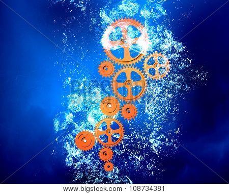 Gears sinking in clear blue crystal water